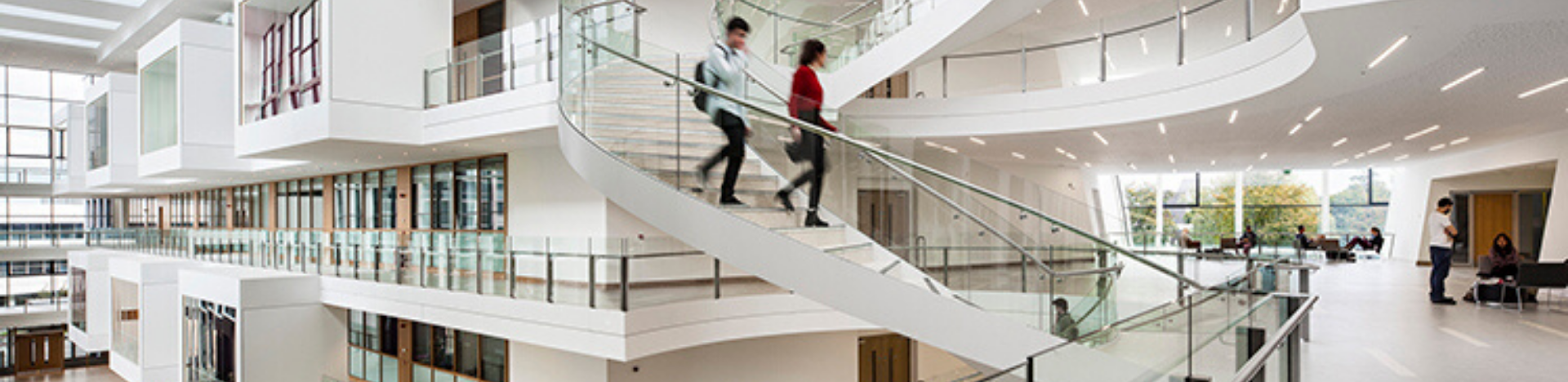 Two students going down the spiral staircase in the UCD O'Brien Centre for Science